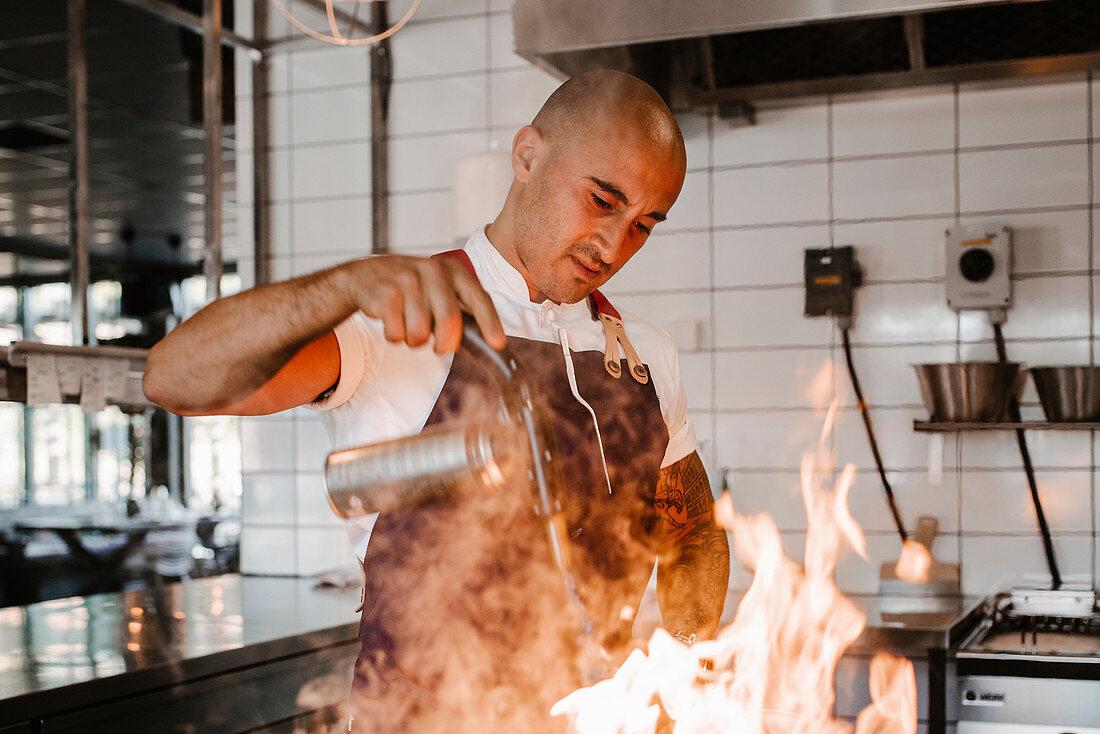 Chef preparing food in kitchen on fire