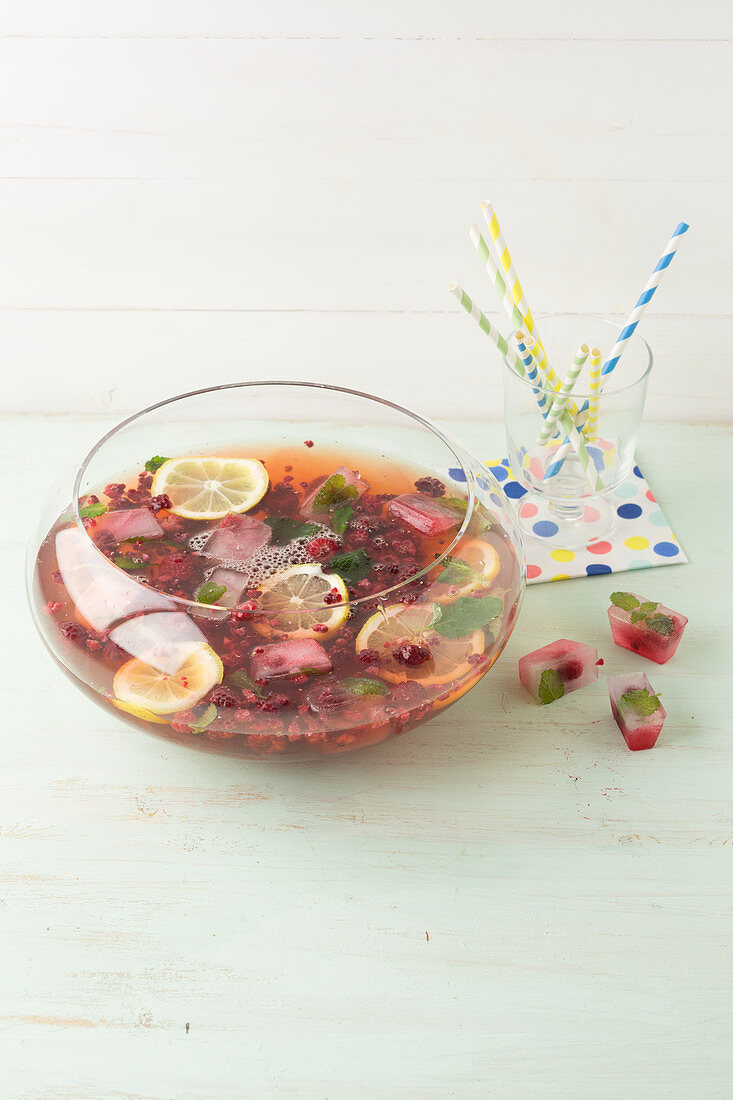 Raspberry tea punch with mineral water, berries and lemon
