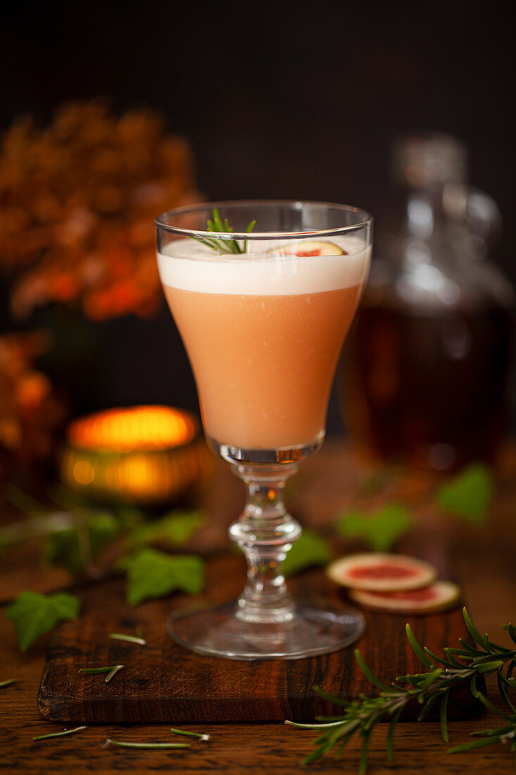 A Bourbon sour cocktail flavoured with fig and rosemary and topped with egg white foam