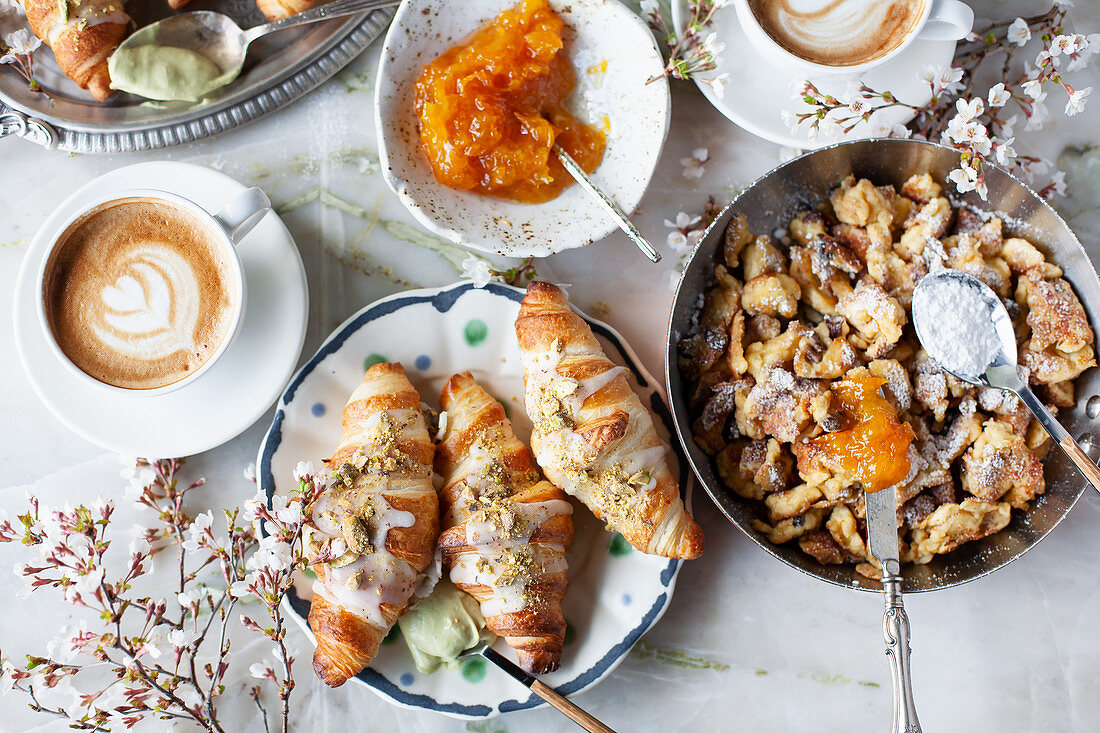Brunch table of Scrambled pancakes (Kaiserschmarrn), almond croissants, and cappuccino
