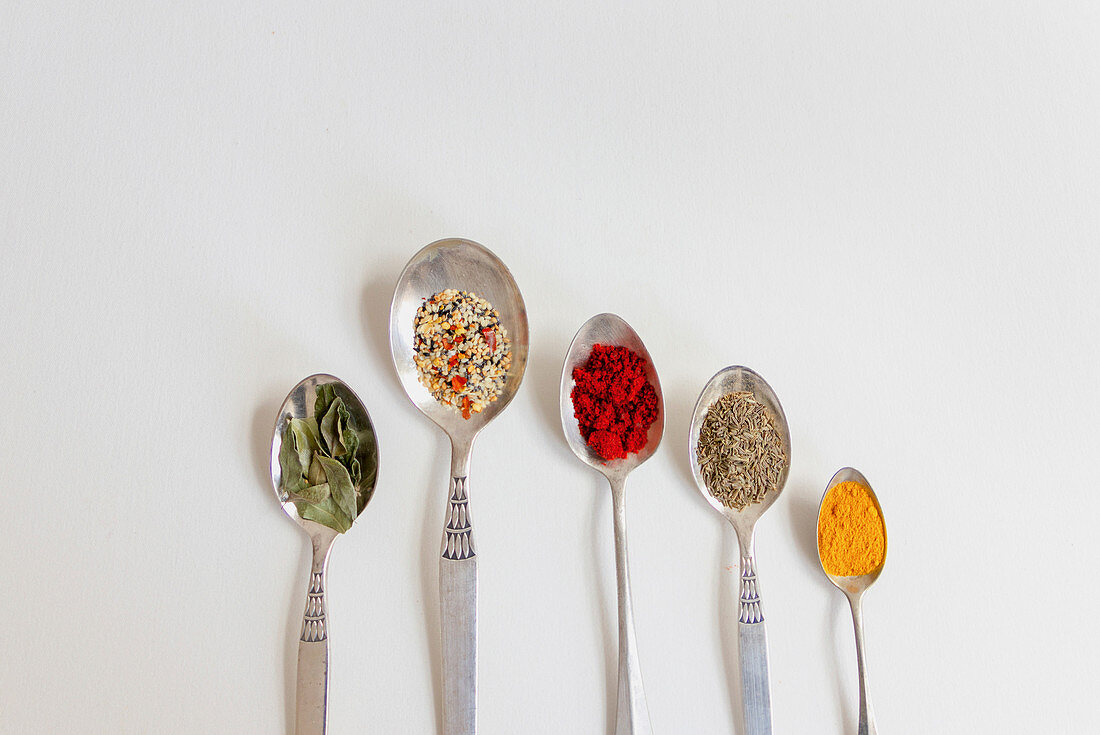 Different condiments on spoons