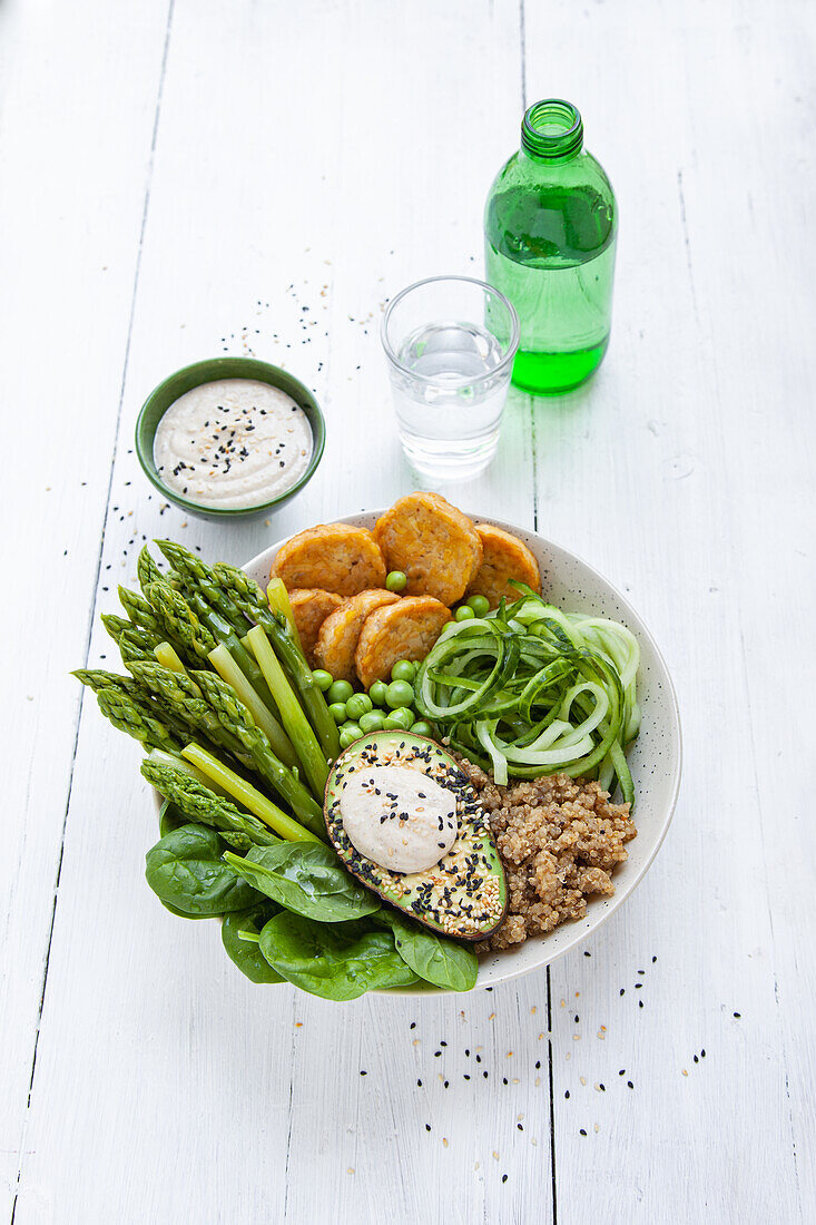 Healthy green bowl with green asparagus, tempeh, quinoa, and tahini dipping sauce