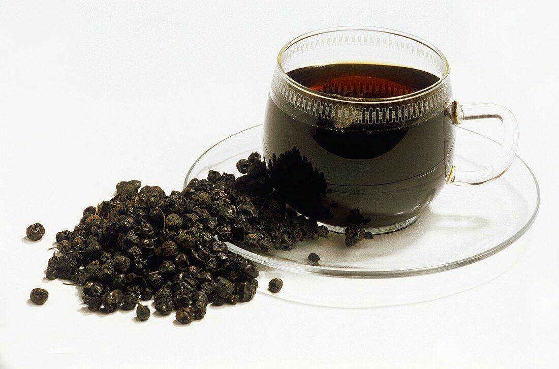 Medicinal tea: buckthorn berry tea in glass cup; berries