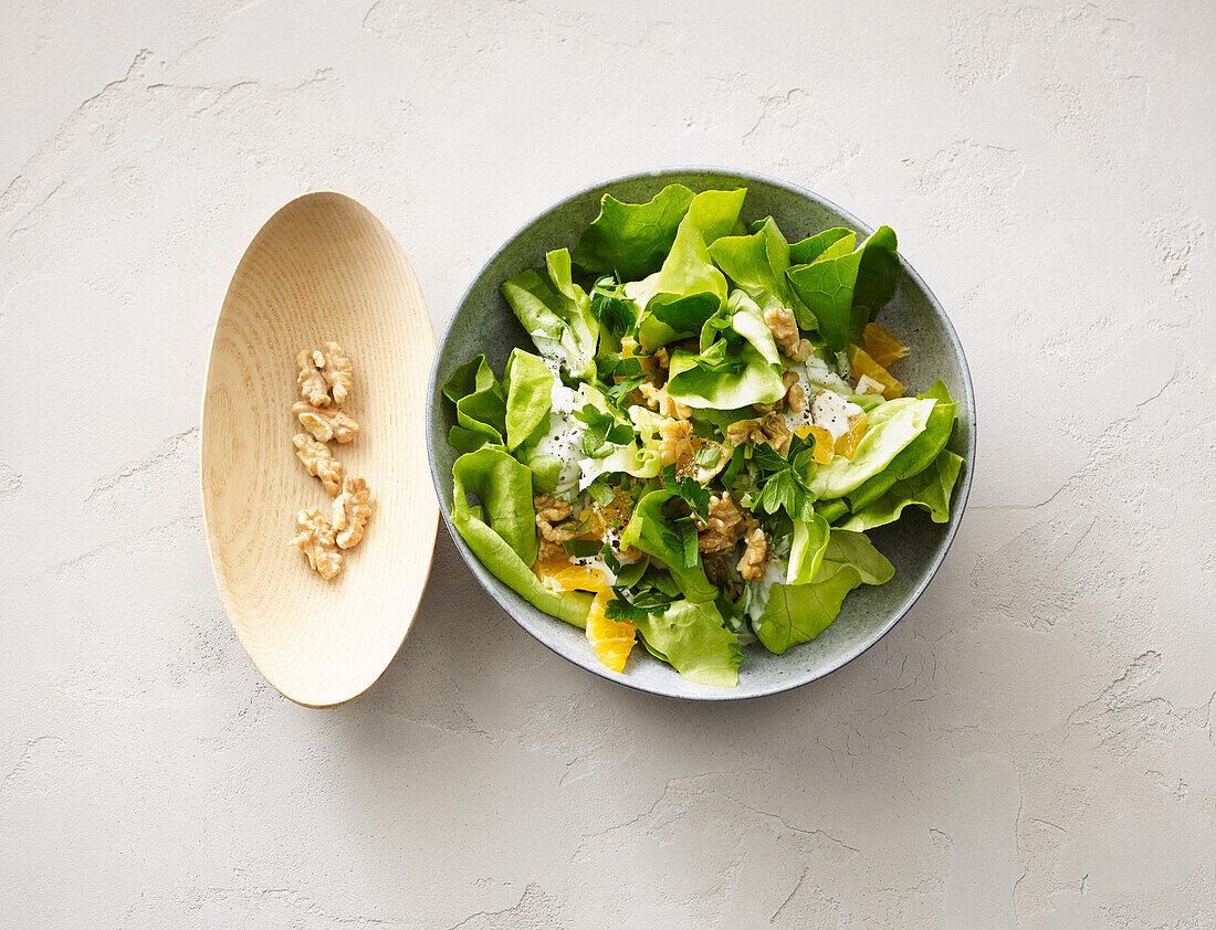 Green salad with mandarins, walnuts and cream sauce