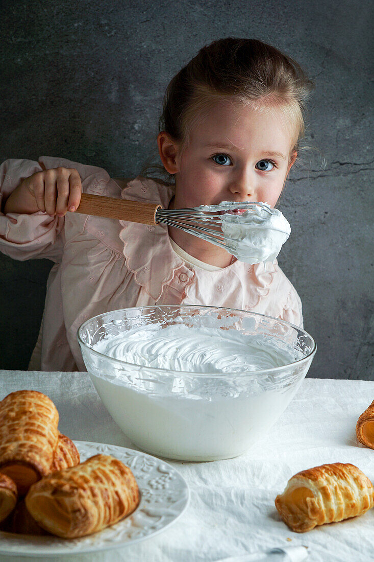 Little girl prepares whipped cream and tastes it straight from the whisk