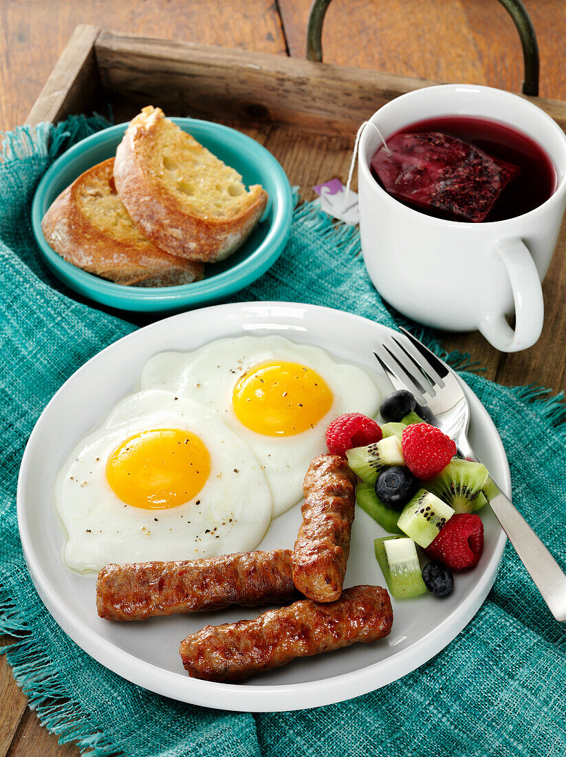 Breakfast sausage with fried eggs and fruits, served with toast and rosehips tea