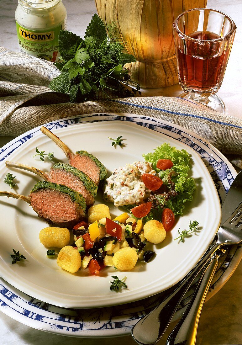 Lamb chops with herb coating, with gnocchi, peppers & olives