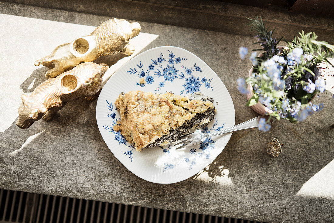 A slice of poppyseed crumble cake on a sunny windowsill