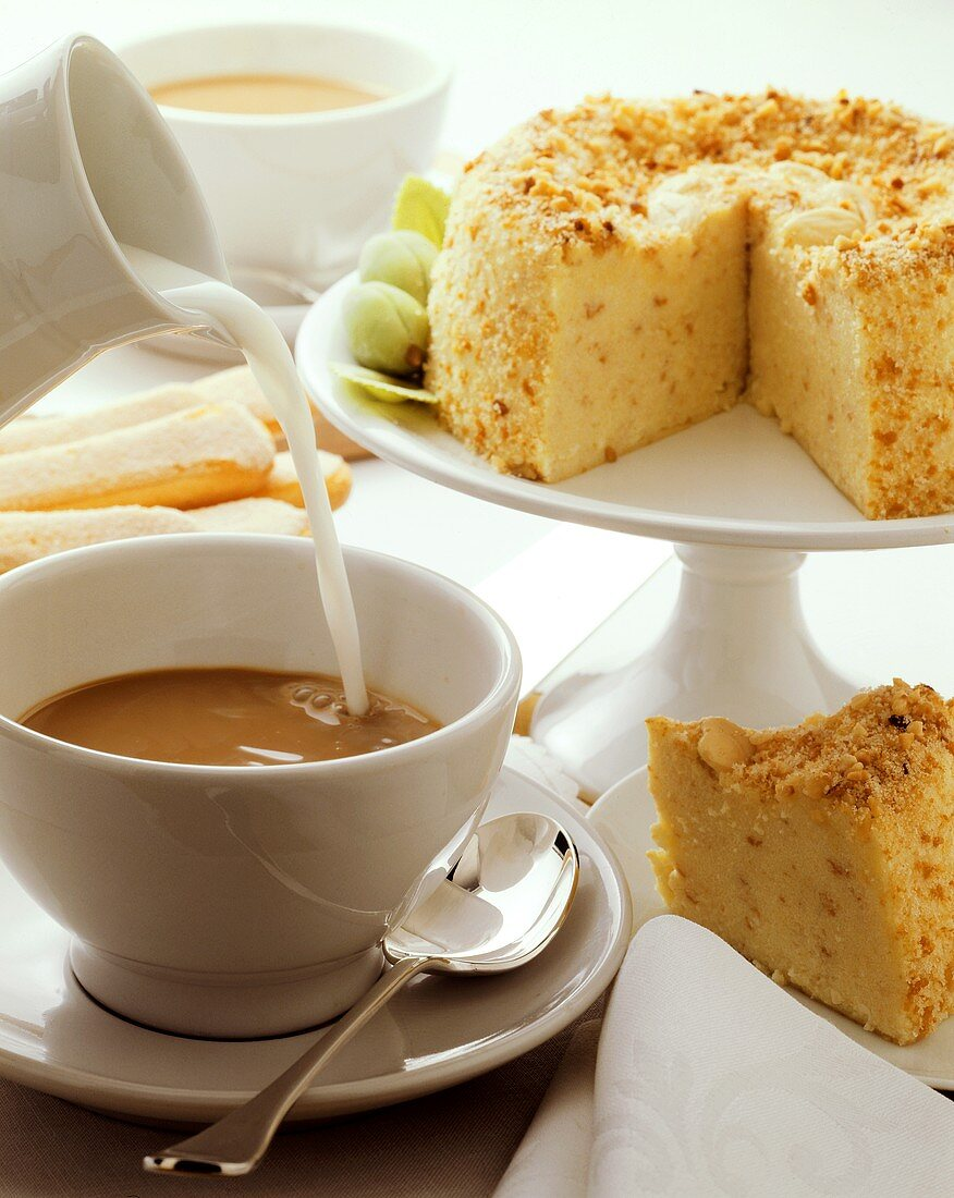 Cup of coffee with milk being poured into it & almond cake