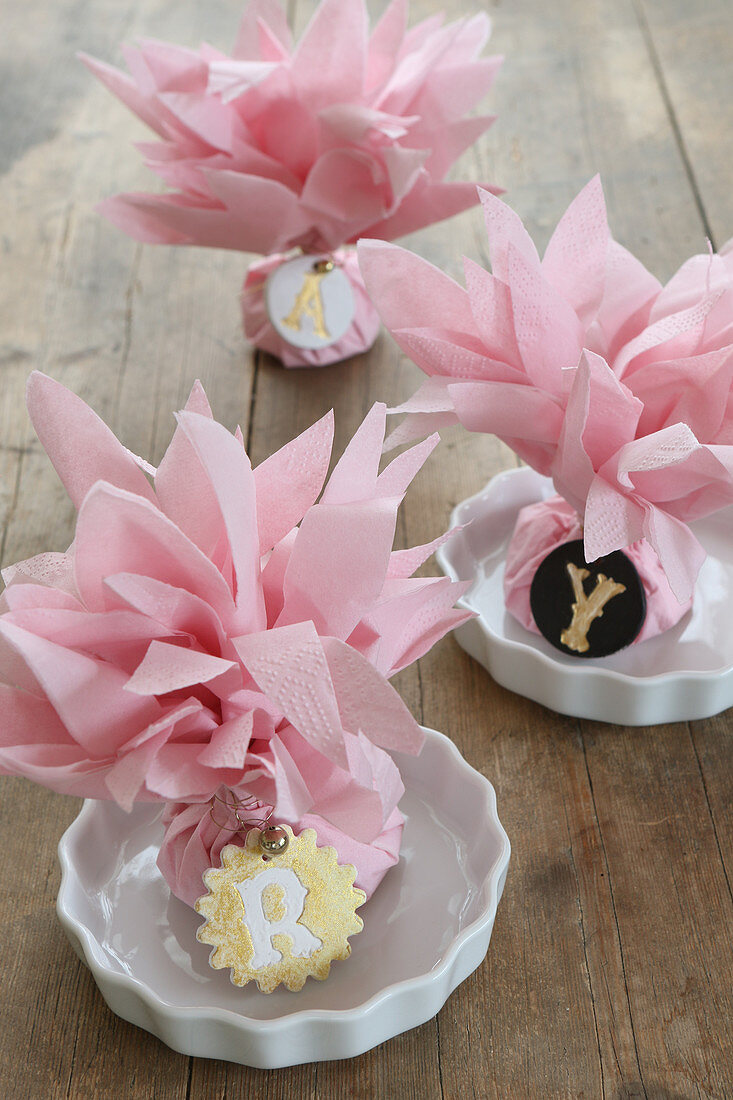 Decorative place cards with napkin flowers and initials made from modelling clay
