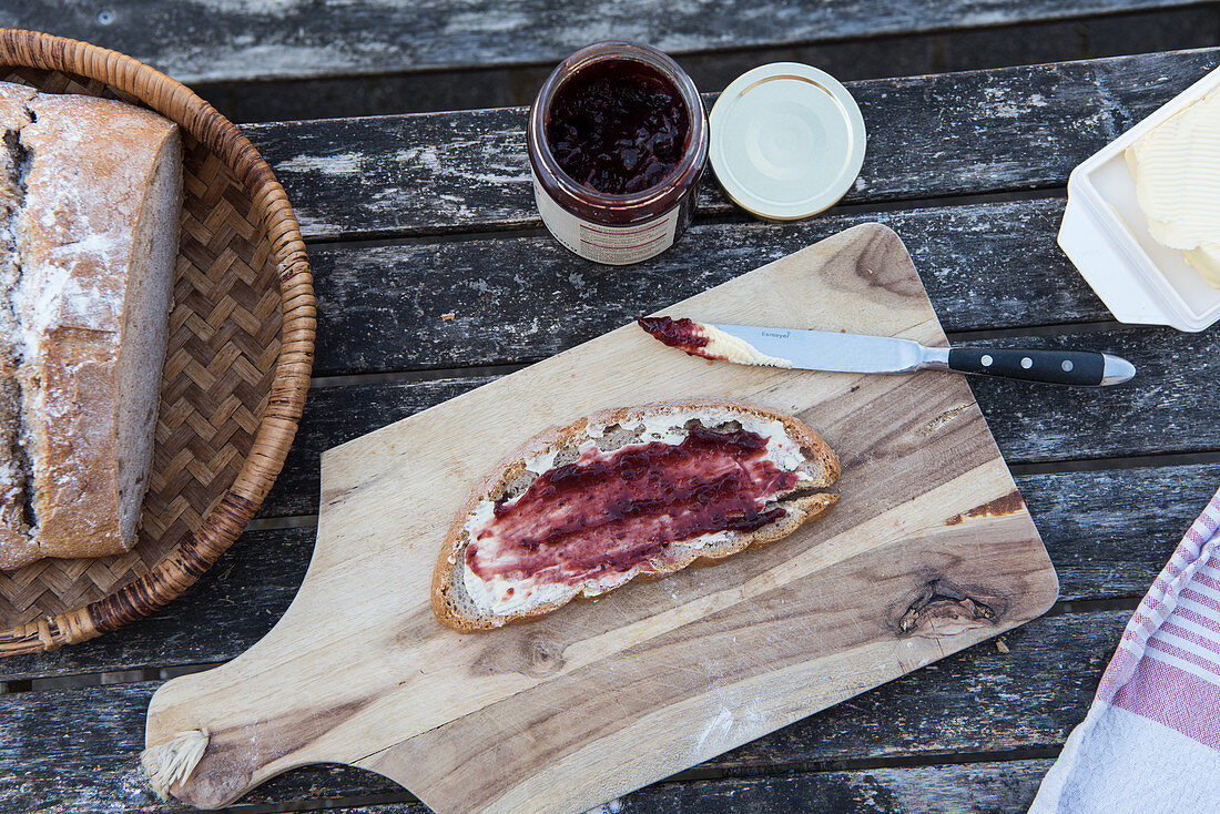 A slice of sour dough bread with butter and jam on a table outside