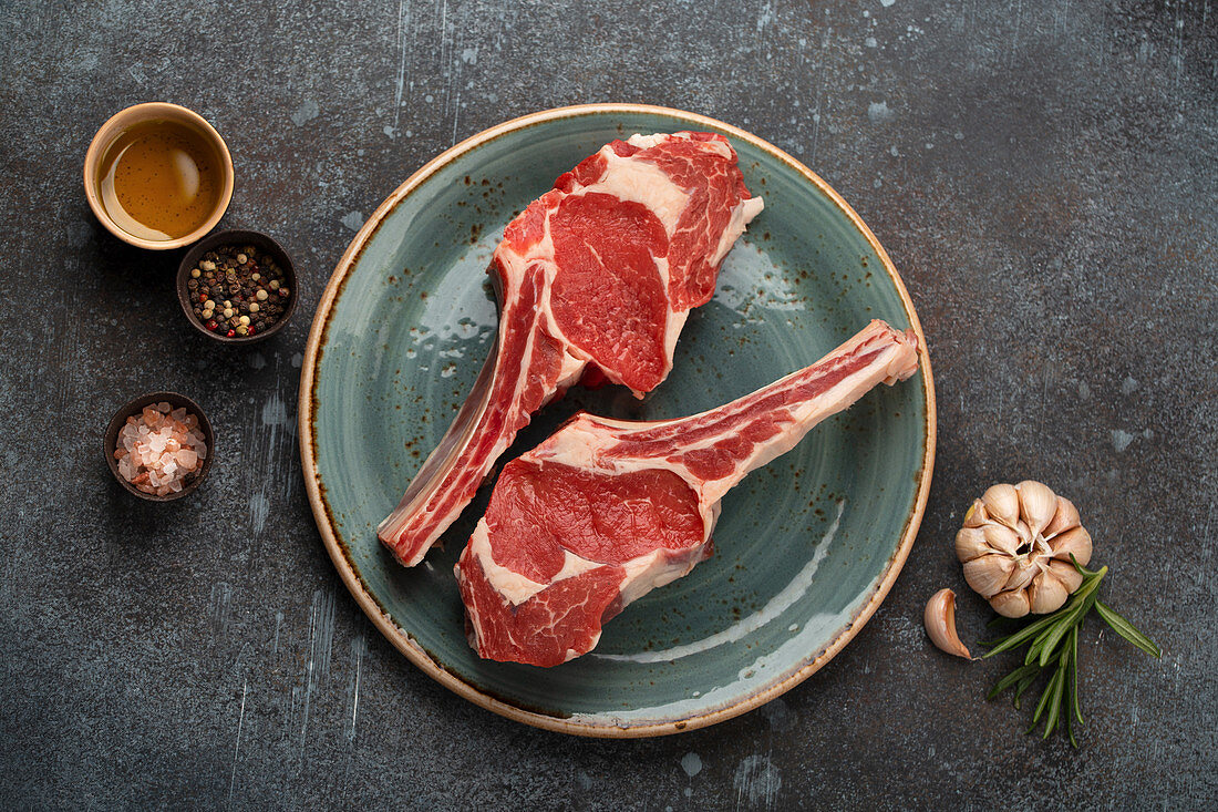 Two raw marbled Tomahawk meat steaks with herbs and seasonings