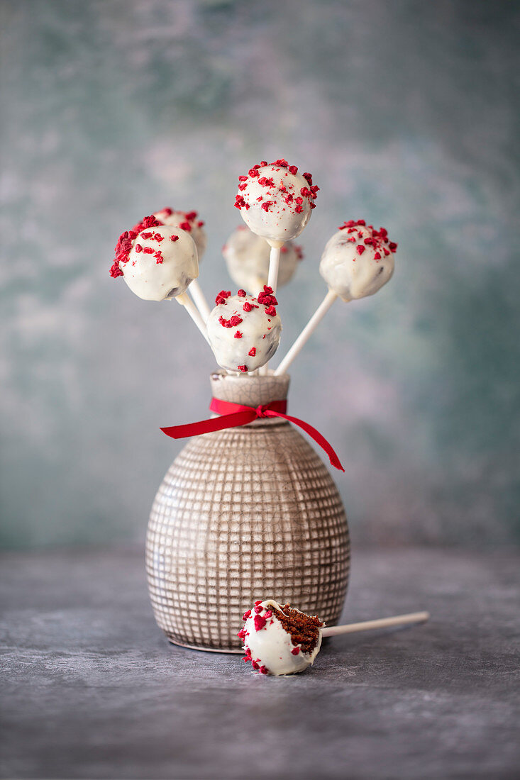 Chocolate vegan cake pops covered with white chocolate and dried raspberries