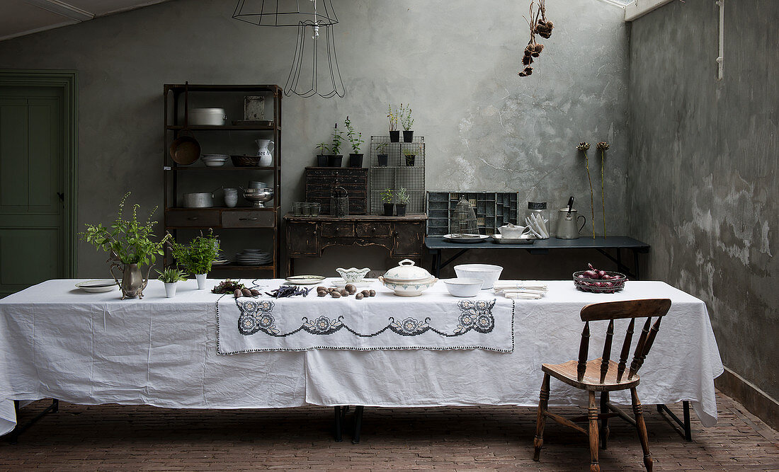 Table set with white tablecloth in dining room with grey walls