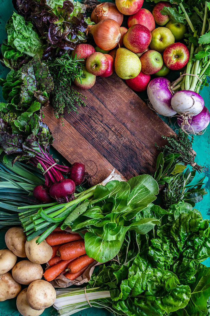 Organic vegetables and fruit with a wooden cutting board