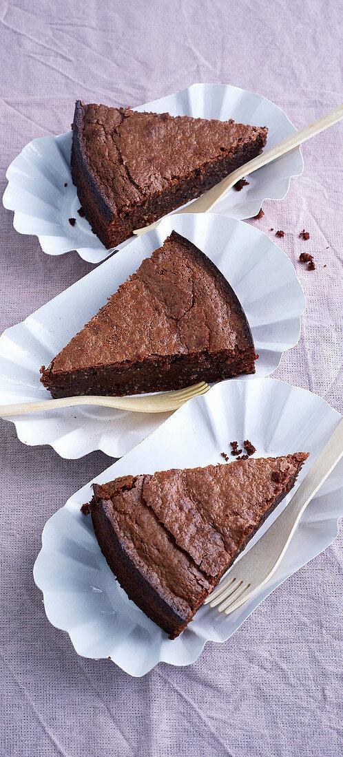 Sliced chocolate cake with amarettini in cardboard bowls