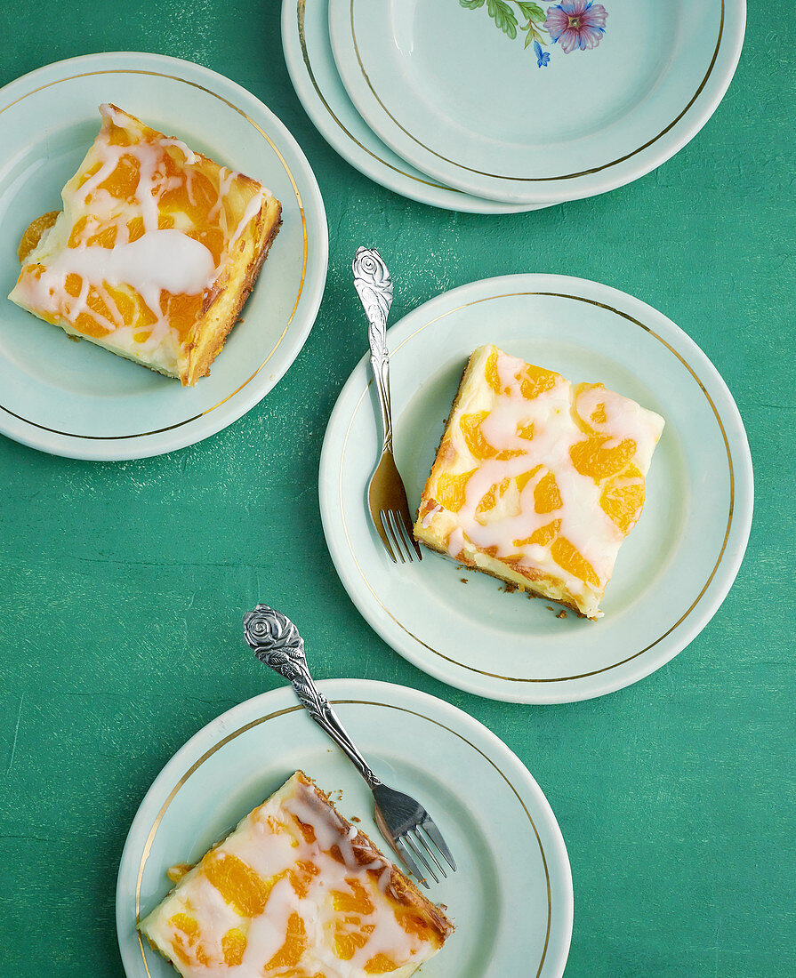 Slices of mandarin cake with sour cream on plates
