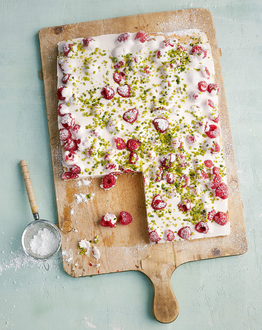 Almond biscuit with raspberry cream and pistachios