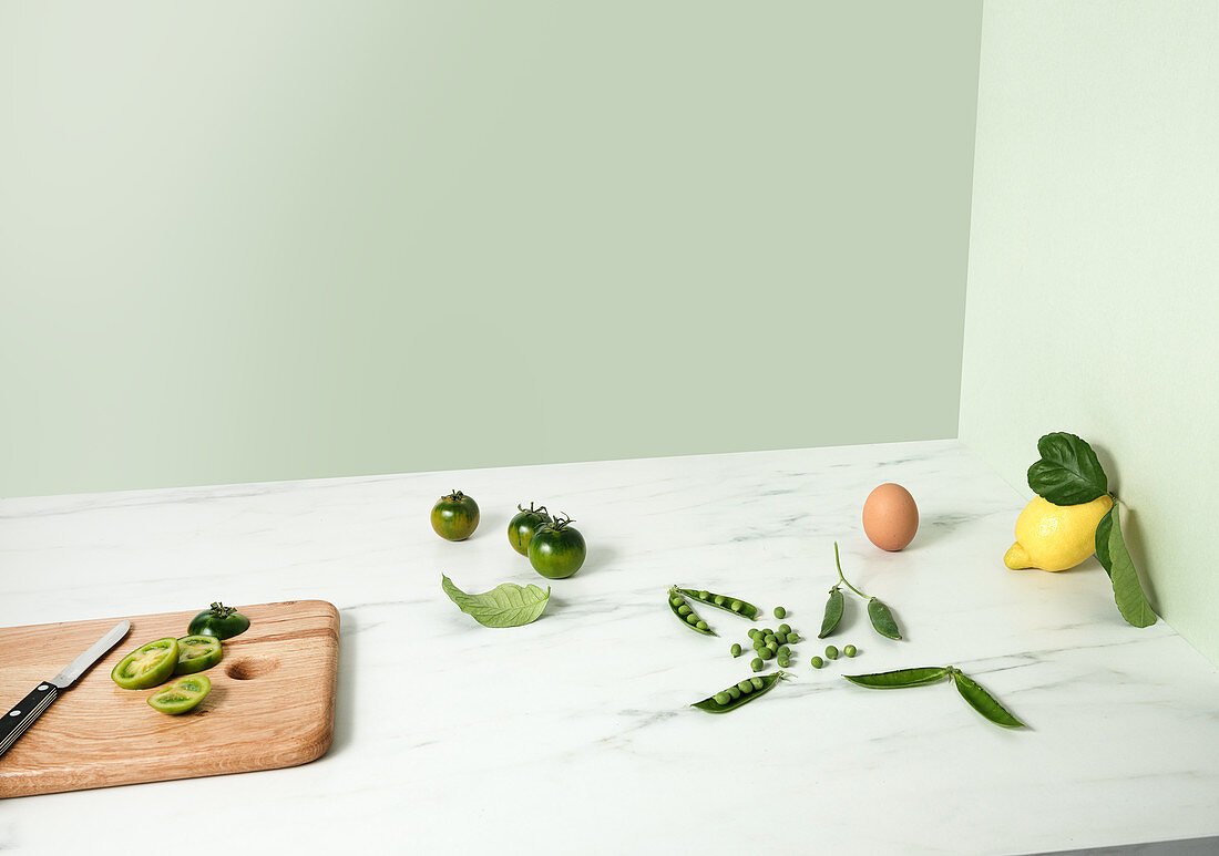 Green tomatoes, peas, an egg and a lemon with leaves