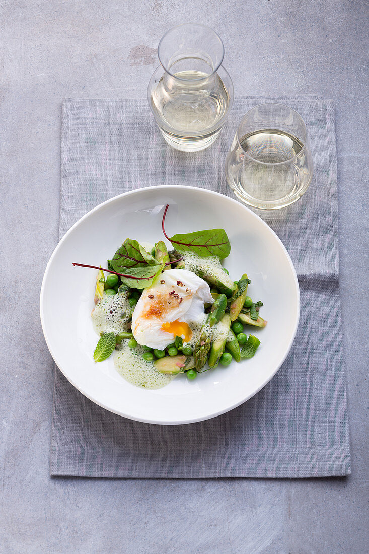 A poached egg with green asparagus and peas