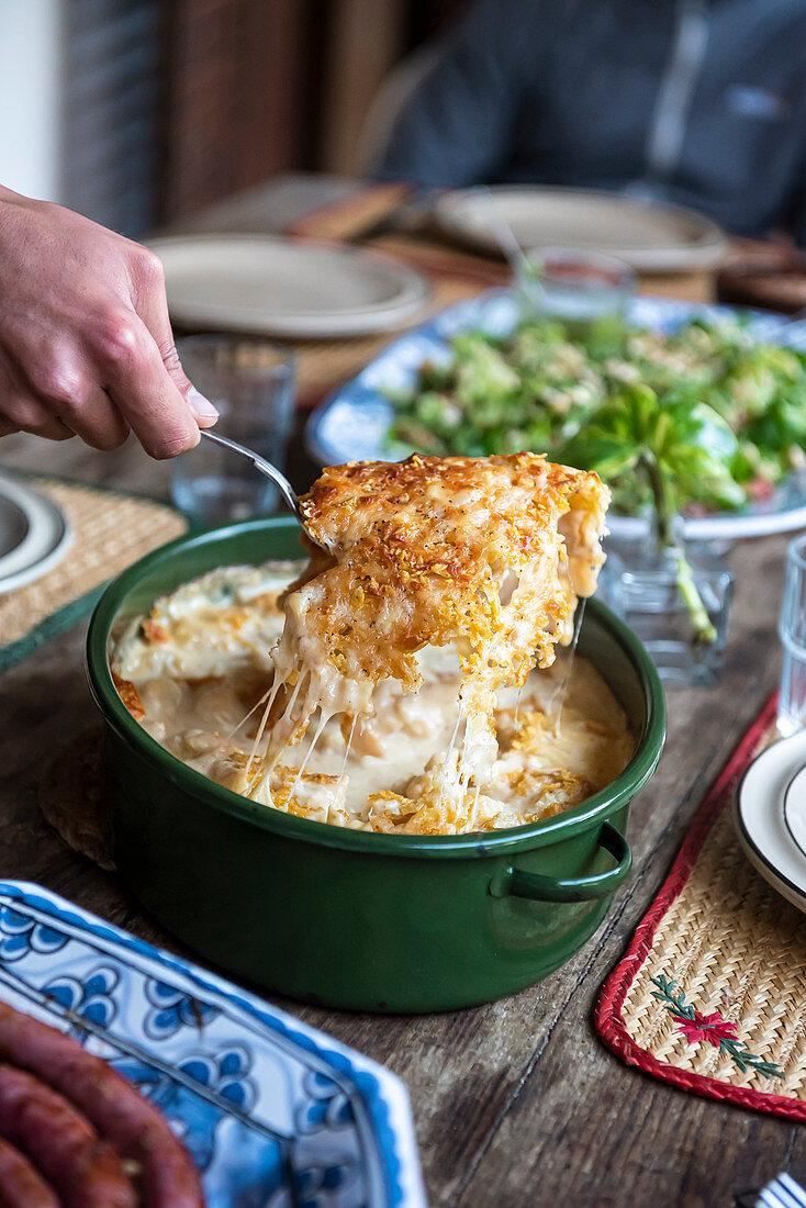 Hand serving cauliflower with cheese