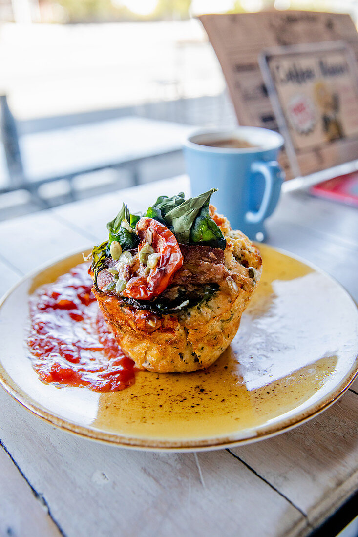 Savoury muffin with bacon and spinach on a restaurant table