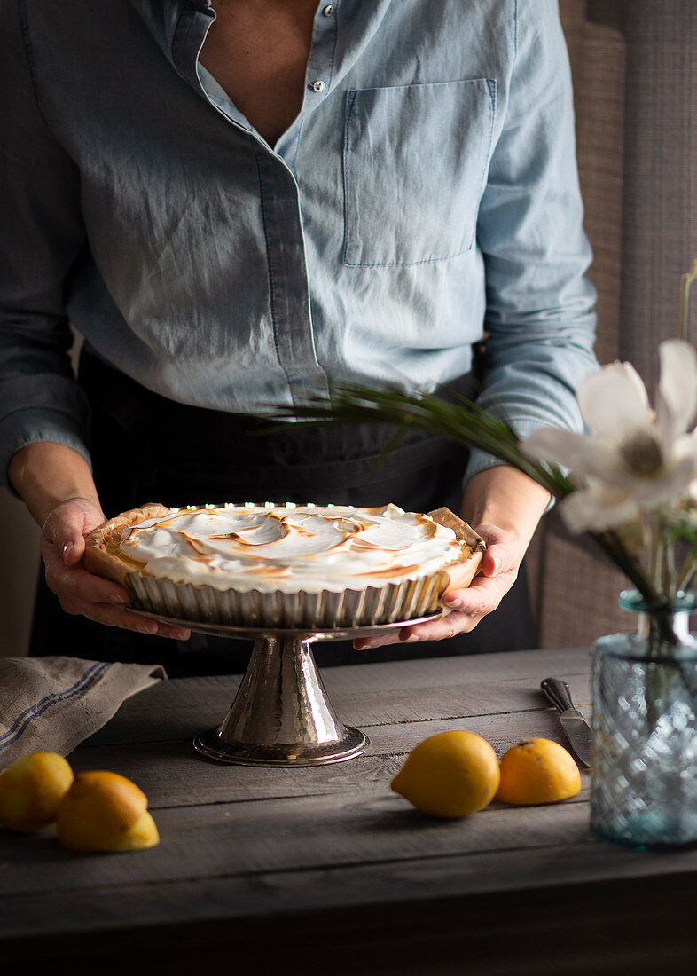Lemon tart with meringue topping on a cake stand