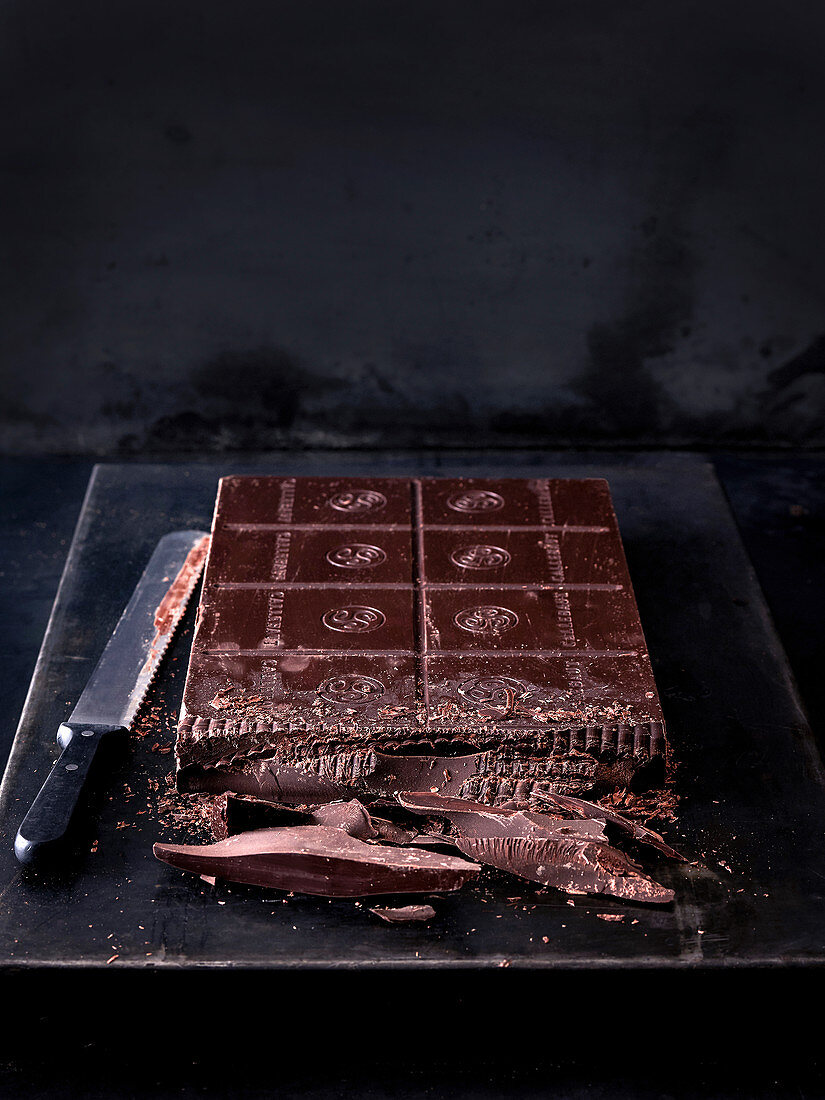 A large block of chocolate on a black baking sheet