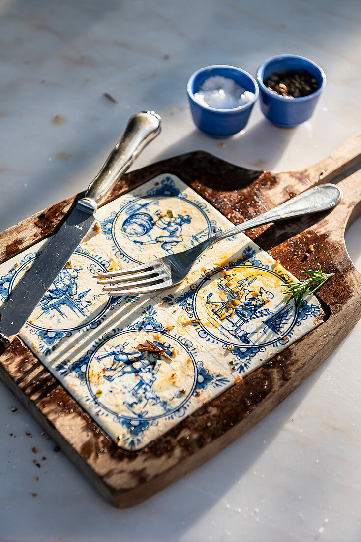 Ceramic and wood board on marble table with remaining oil and cutlery after eating a steak
