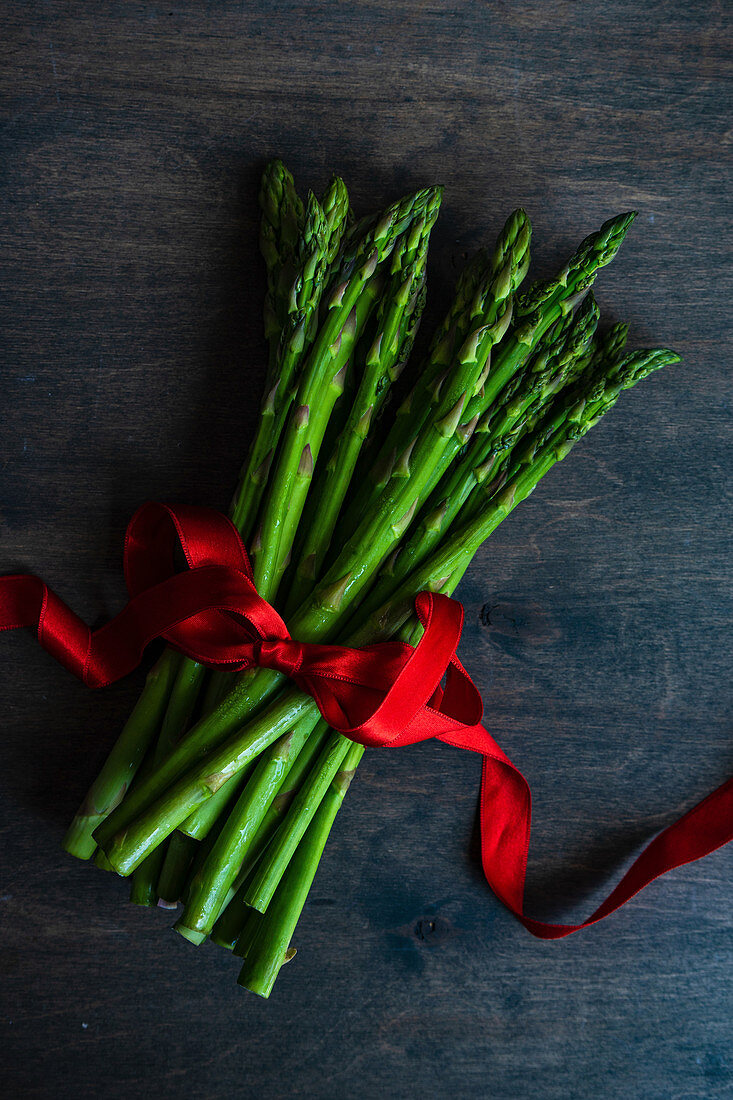 Organic food concept with asparagus and red ribbon