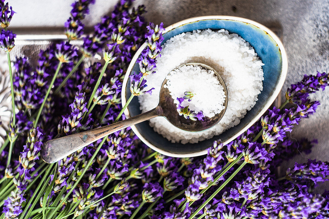 Healthcare concept with fresh lavender flowers and sea salt on stone background with copy space