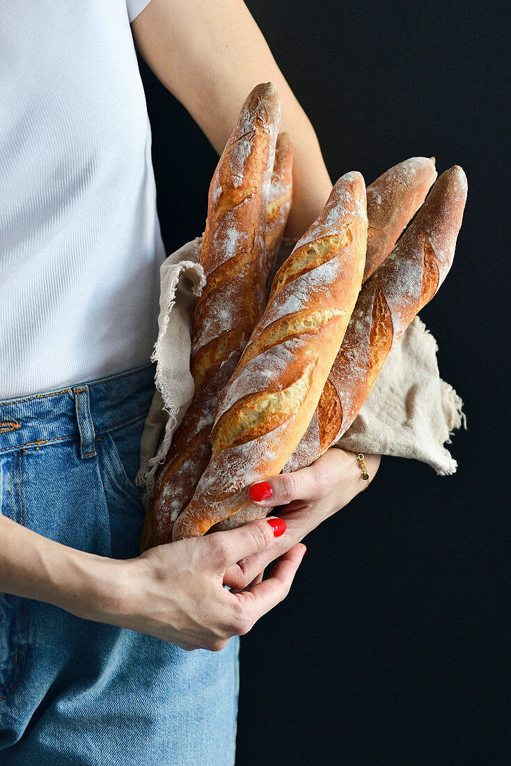 Woman holding French baguettes