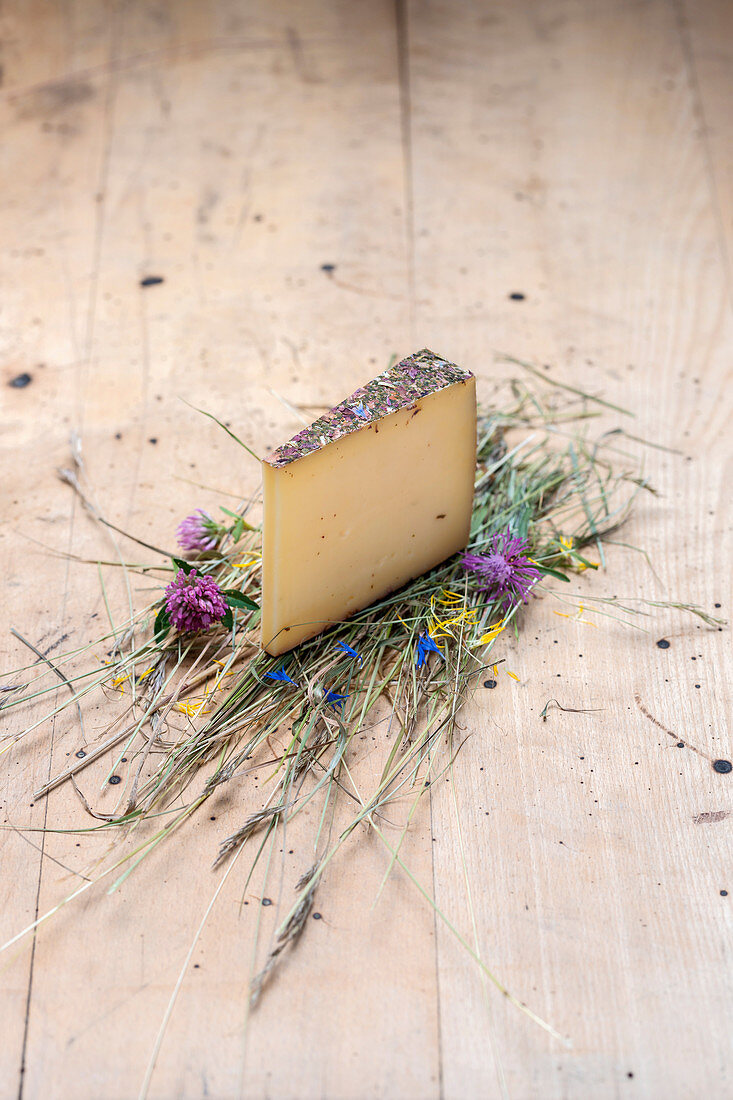 A piece of hay milk cheese on a wooden surface