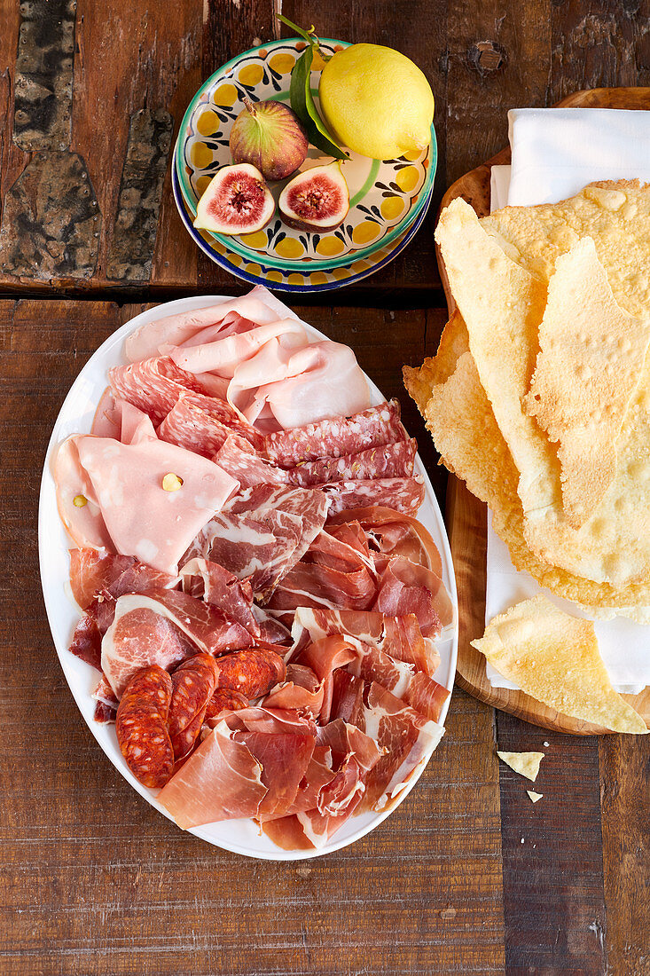 Cold meat platter, figs, lemon and Sardinian flatbread