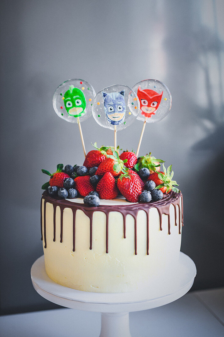 Dripping cake decorated with berries and lollies