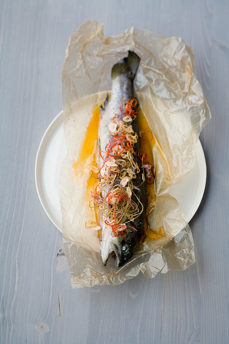 Brown trout in parchment with chilli and ginger
