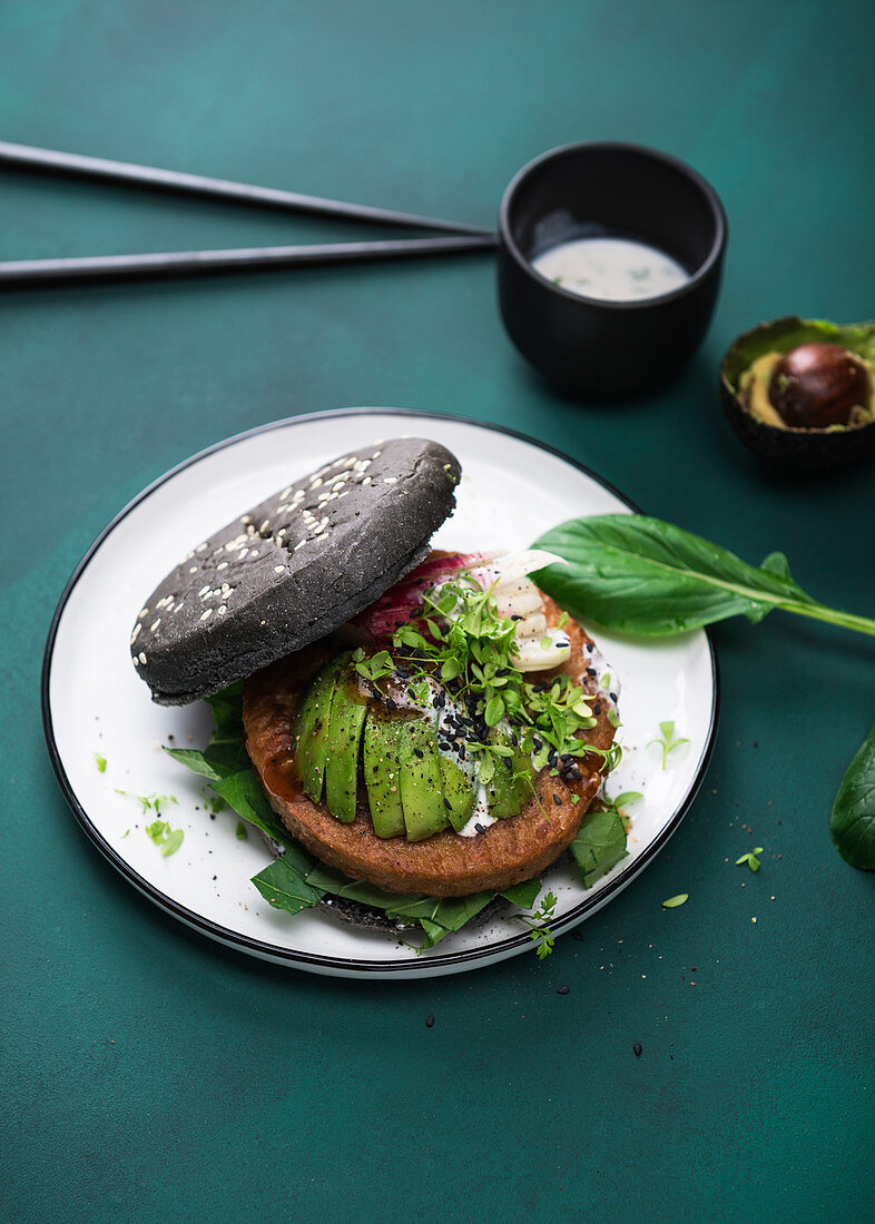 Soy wheat protein patty with avocado, radishes and two sauces in a black burger bun