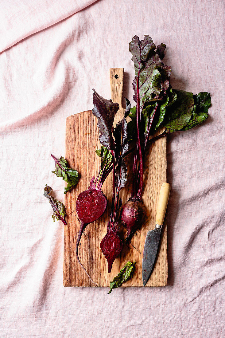 Beets with a knife on a wooden cutting board.