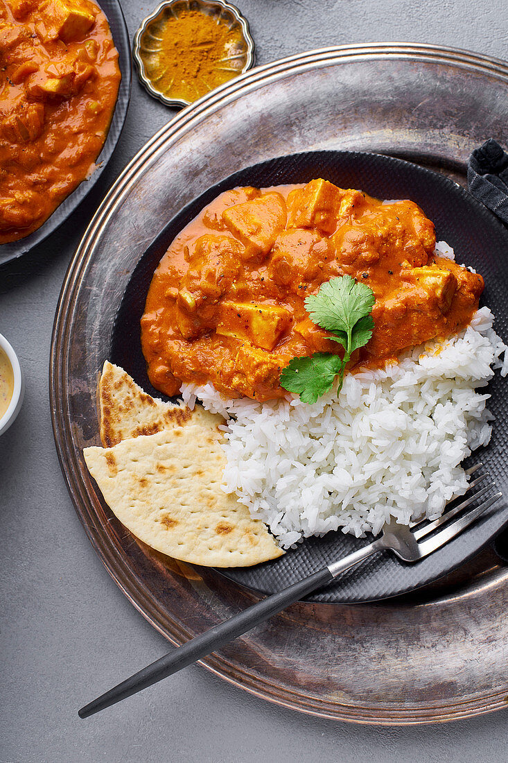 Paneer tikka masala with basmati rice, Indian cuisine, vegetarian dish made of soft cheese cubes cooked in spicy tomato sauce with cream