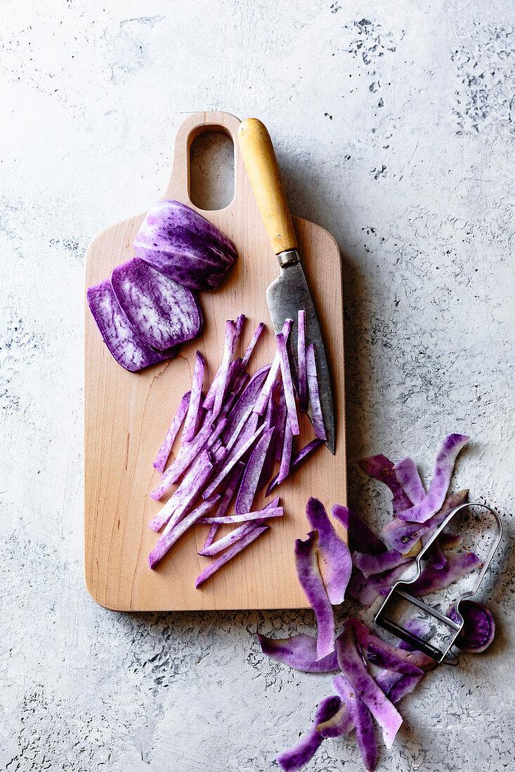 Purple daikon cut into julienne strips on a wooden cutting board.