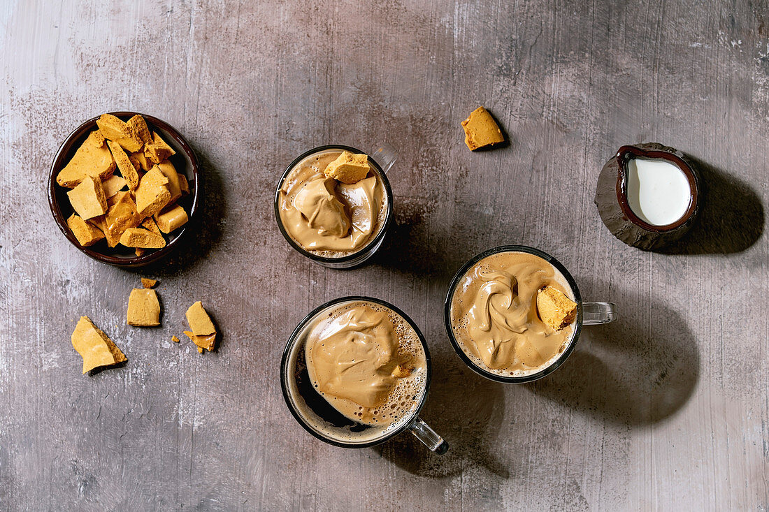 Dalgona frothy coffee trend korean drink latte espresso with coffee foam in three different glass cups, decorated by dalgona cinder toffee candy. Grey concrete background. Flat lay, space