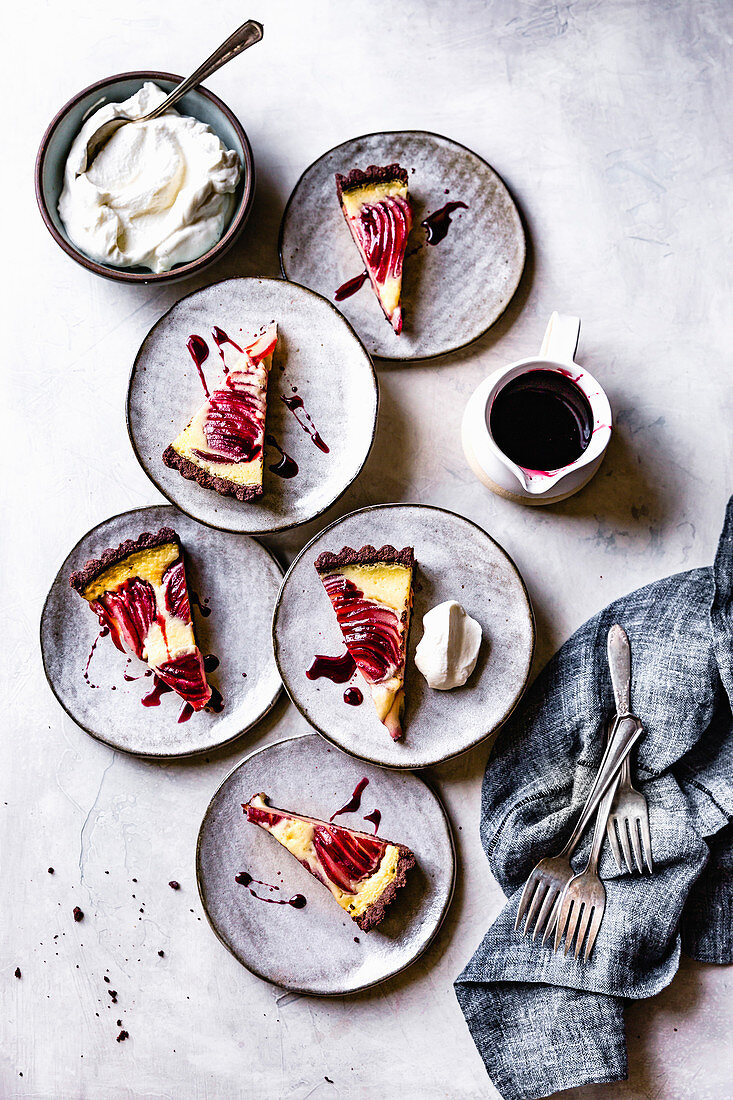 Servings of red wine poached pear custard tart with creme fraiche and raspberry sauce.