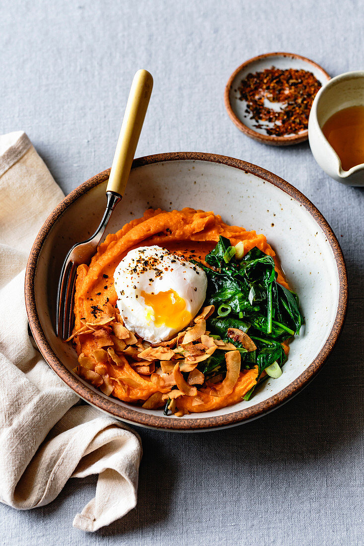 Closeup view of a sweet potato breakfast bowl with coconut bacon, spinach and poached egg.