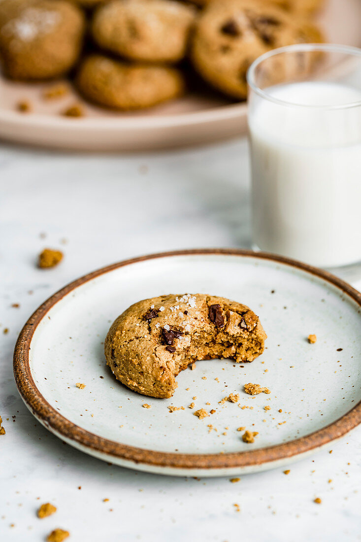 A bitten chocolate chip cookie with almond butter and salt