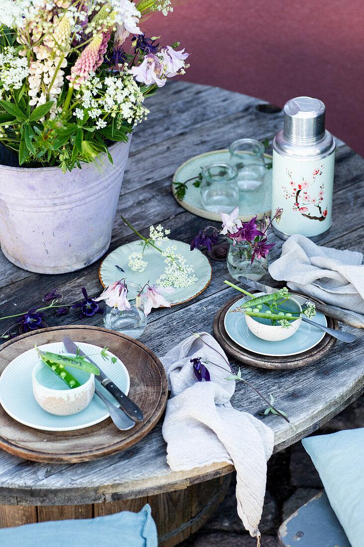 Ländliches Tischgedeck mit Erbsenschoten als Platzkarten, Frühsommer-Strauß aus Lupinen, Akelei, Gerste und Wiesenkümmel im Zinkeimer