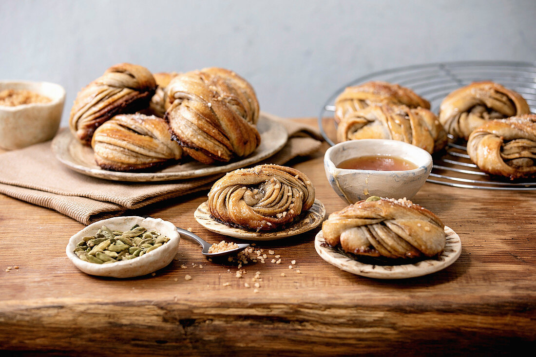 Traditional Swedish cardamom sweet buns Kanelbulle on plate, ingredients in ceramic bowl above on wooden table.