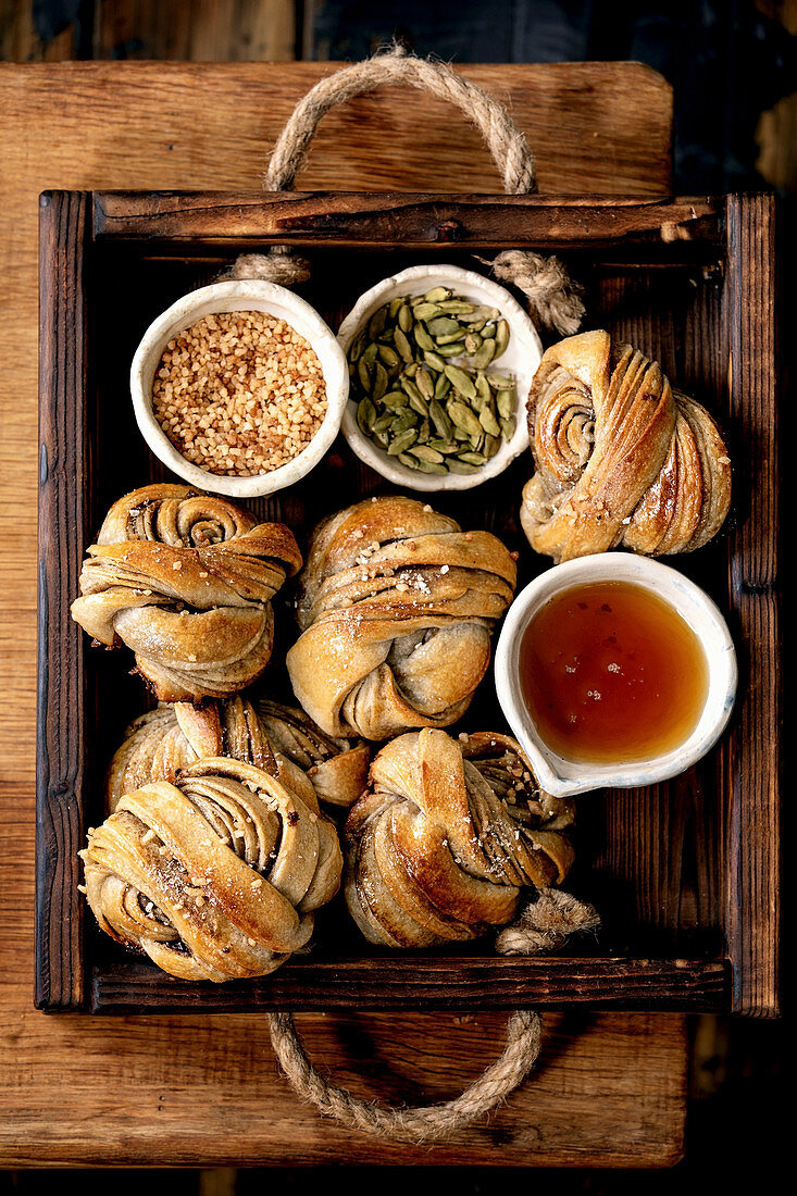 Traditional Swedish cardamom sweet buns Kanelbulle in wooden tray, ingredients sugar, cardamom and syrup in ceramic bowl on wooden table. Flat lay, space