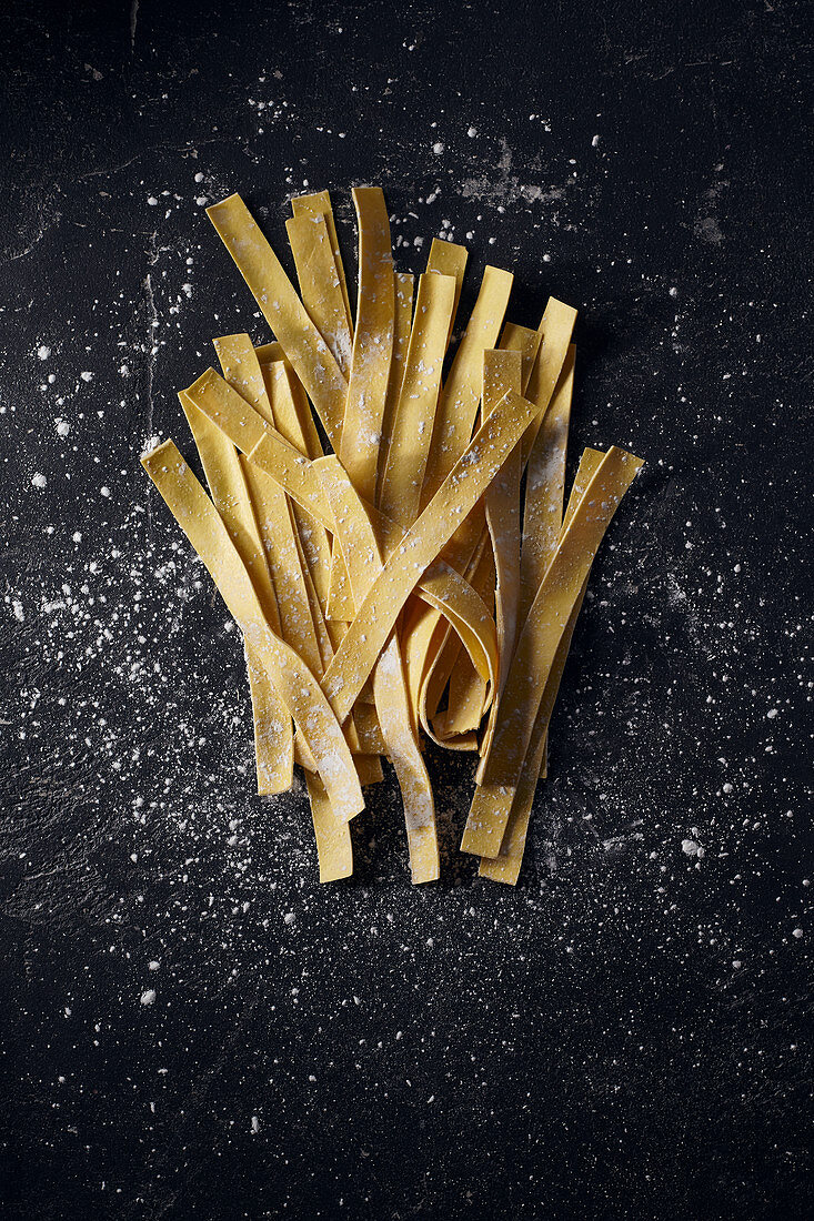 Uncooked fresh ribbon pasta on a dark surface