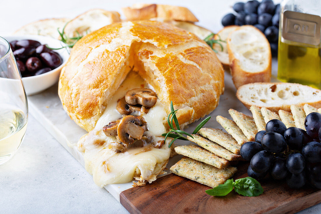 Baked brie wrapped in puff pastry with mushrooms with bread and cracker on a board