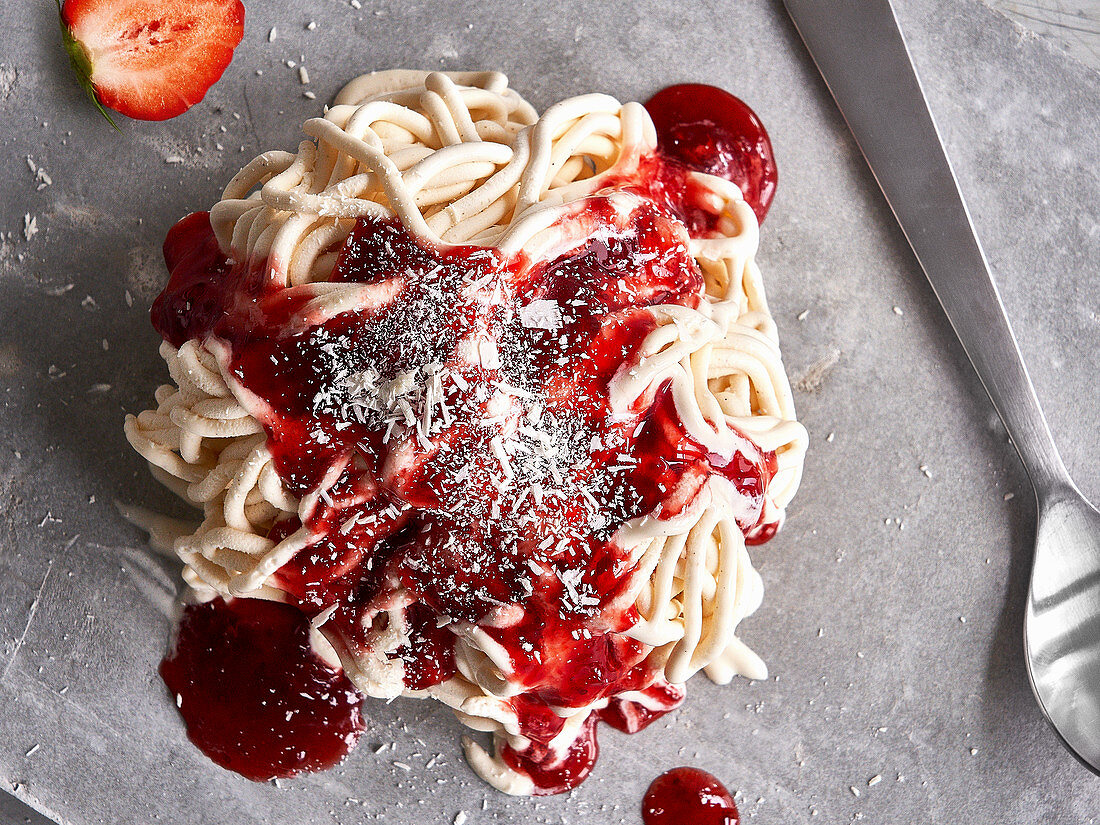 Homemade spaghetti ice cream with strawberry sauce